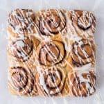 Nine vegan banana bread cinnamon rolls with vanilla glaze on a sheet of baking parchment.