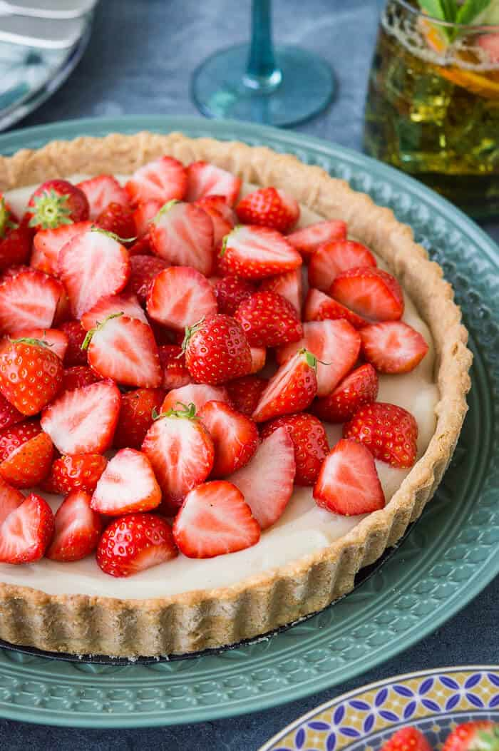 Close up shot of fresh strawberries piled on top of a vegan tart with coconut pastry cream.