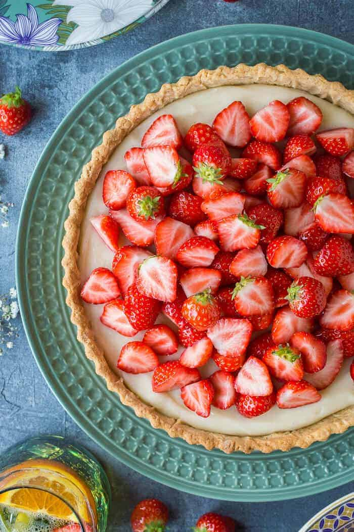 Close up of vegan strawberry tart on a green plate.