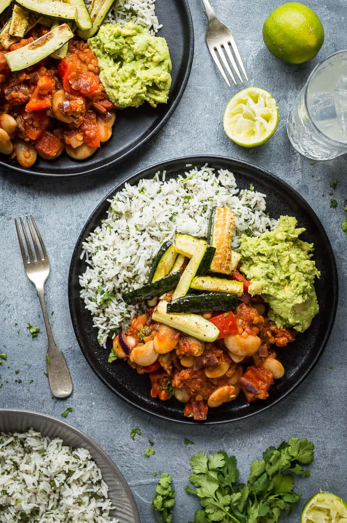 Two black plates of vegan lentil, vegetable and butter bean chilli, coriander rice, guacamole and roasted courgette on a grey background.