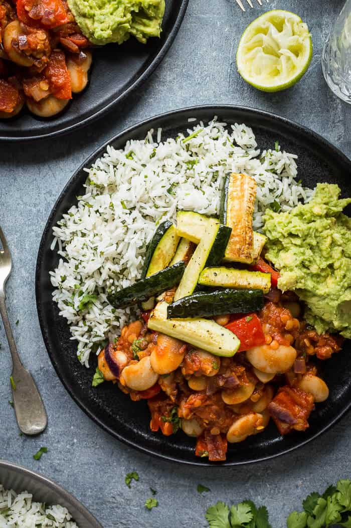 Close up of a black plate full of chilli, coriander rice, guacamole and roasted courgette.