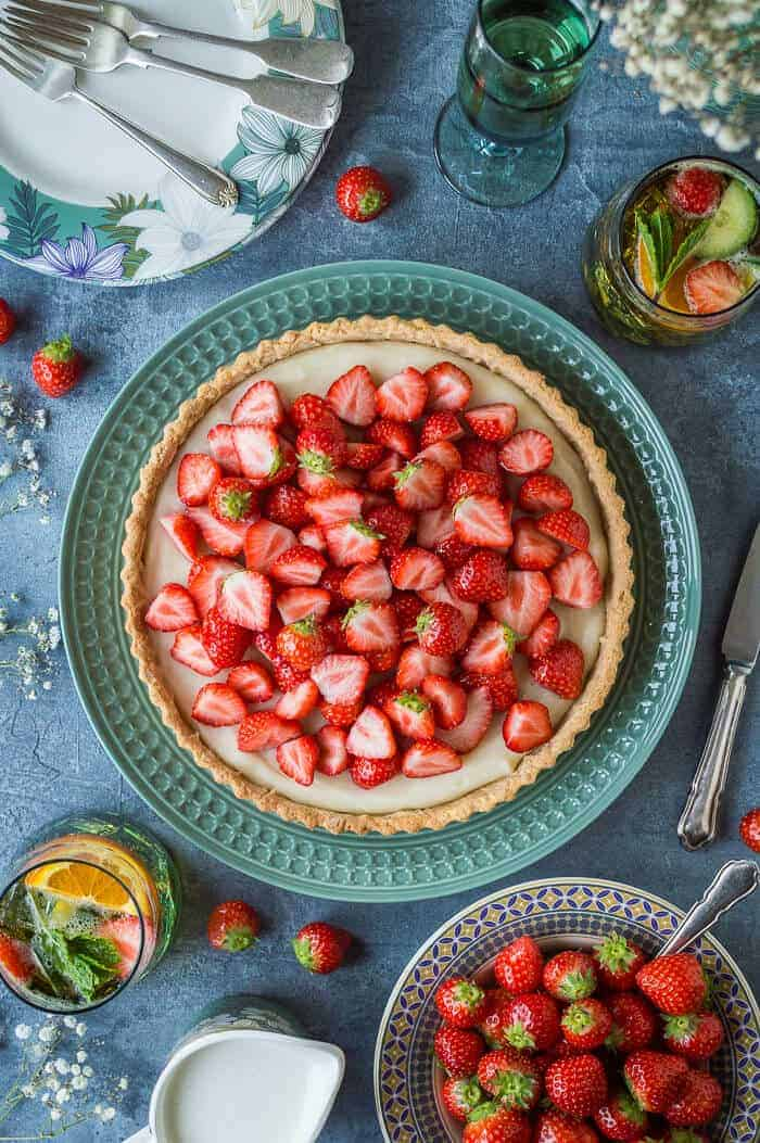 Vegan strawberry tart on a green platter with a bowl of strawberries and glasses of Pimms.