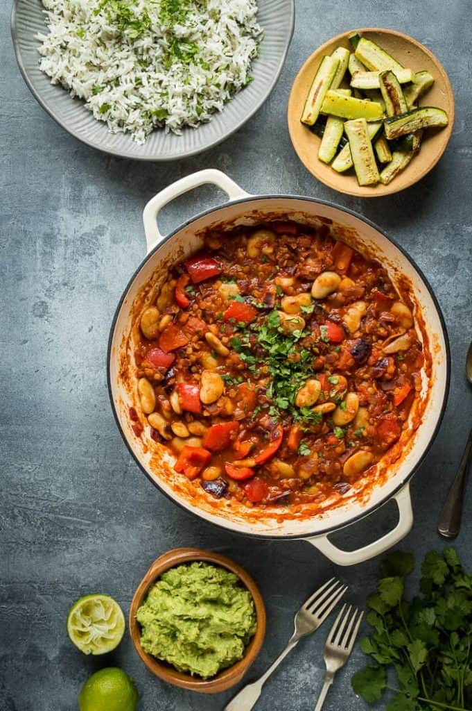 A pan of vegan vegetable, lentil and butter bean chilli with a bowl of coriander rice, roasted courgettes and guacamole on a grey background.