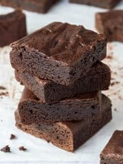 A stack of four chewy vegan brownies.