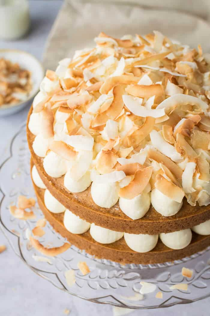 Close up of the toasted coconut flakes on top of a vegan coconut layer cake.