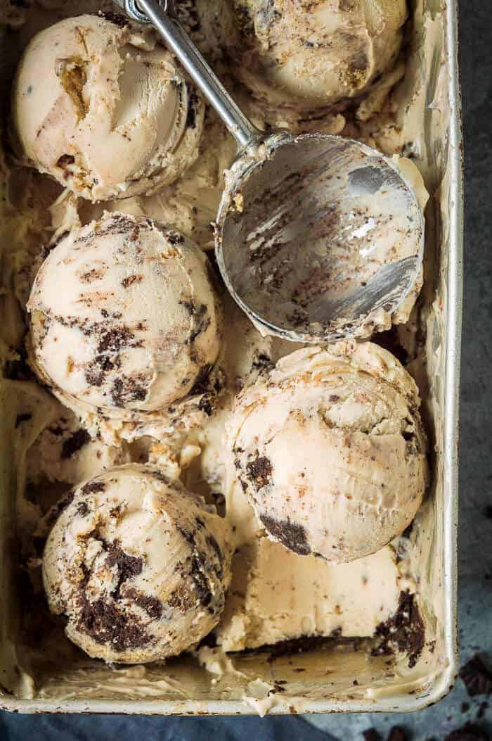 Close up of scoops of peanut butter and cookies ice cream in a metal dish.