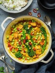 A white cast iron pan full of vegan lemongrass coconut curry with a grey bowlful of rice.