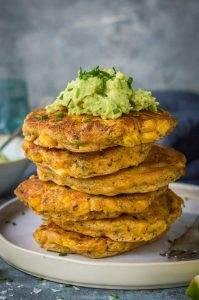 A stack of easy vegan corn fritters topped with guacamole on a white plate.