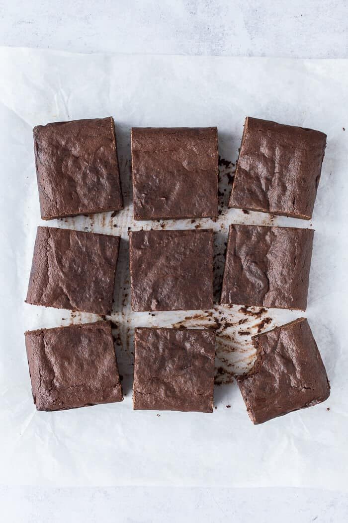 Nine fudgy vegan brownies on a sheet of baking parchment.