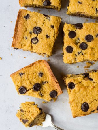 A square of vegan, gluten free, low fodmap sweet potato chocolate chip cake on a sheet of baking parchment with a forkful removed.