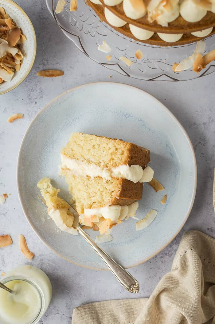 Top down shot of a slice of coconut cake on a grey plate on a grey background.