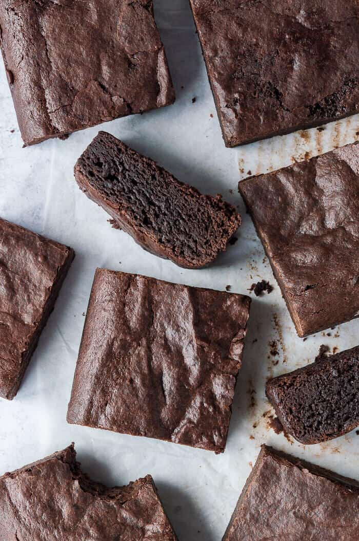 Vegan brownies on a sheet of baking parchment, two on their side.