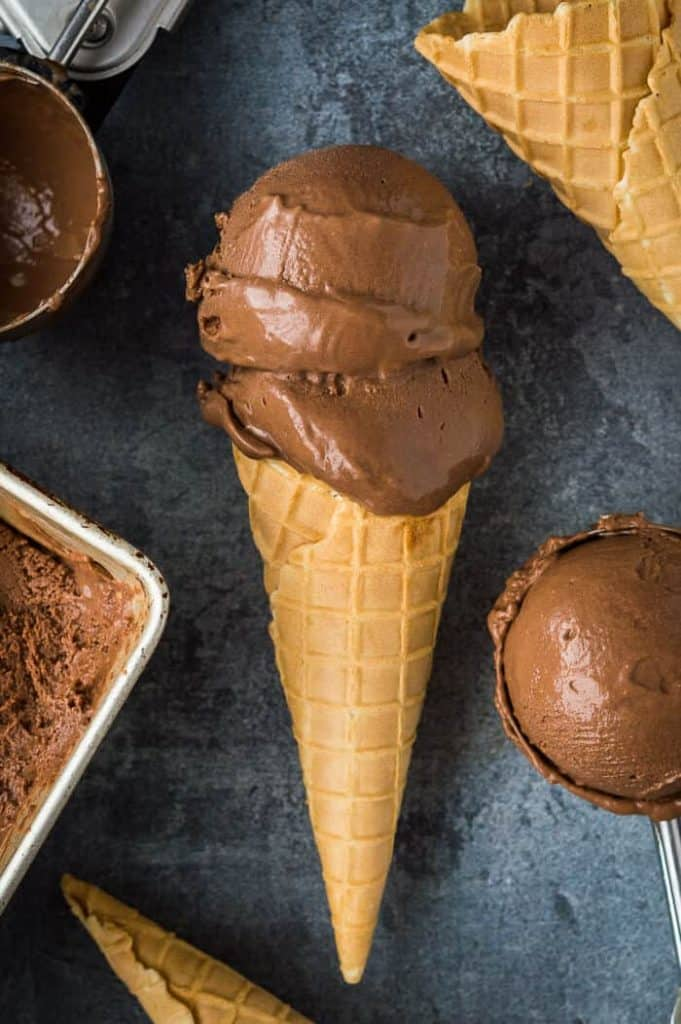 A cone of vegan chocolate ice cream with two scoops on a grey background surrounded by more ice cream and cones.