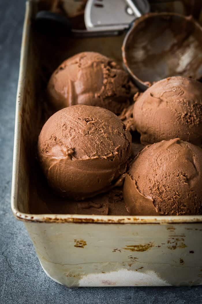 Scoops of creamy vegan chocolate ice cream in a metal loaf tin.