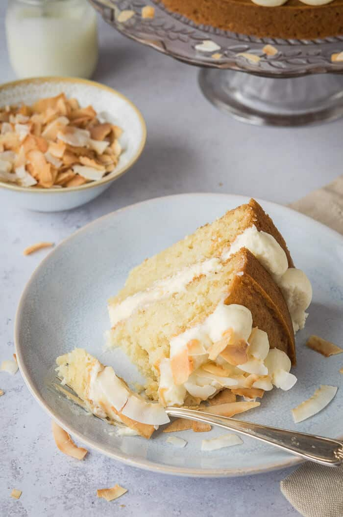 A sliceof vegan coconut layer cake on a grey plate with a bowlful of toasted coconut flakes.