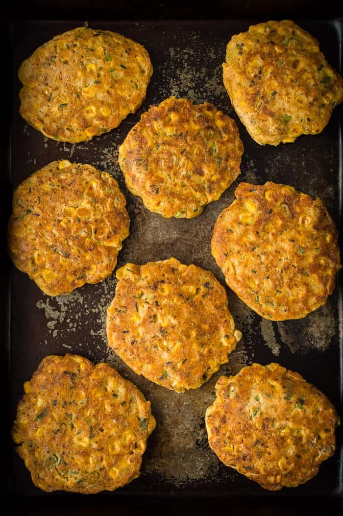 Vegan sweetcorn fritters on a dark baking tray.