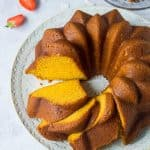 Sliced vegan mango bundt cake on a white plate.