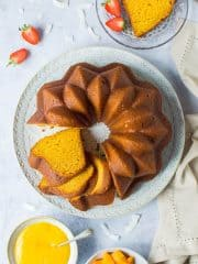 vegan mango bundt cake on a white plate on a grey background with strawberries, sliced mango and mango curd.
