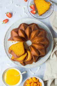 vegan mango bundt cake on a white plate on a grey background with strawberries, sliced mango and mango curd.