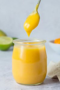 a small jar of vegan mango curd with a spoonful being taken out.