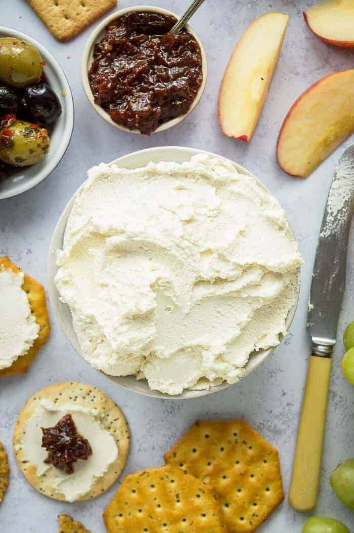 A bowl of almond feta cream cheese surrounded by crackers, apple slices, olives, a knife and a bowl of chutney