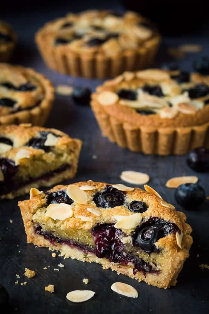 Close up of a blueberry frangipane tart sliced in half.