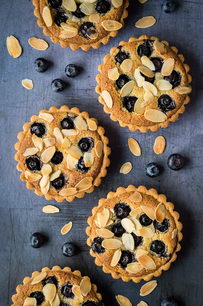 Blueberry bakewell tarts in a line on a metal background with blueberries and flaked almonds.