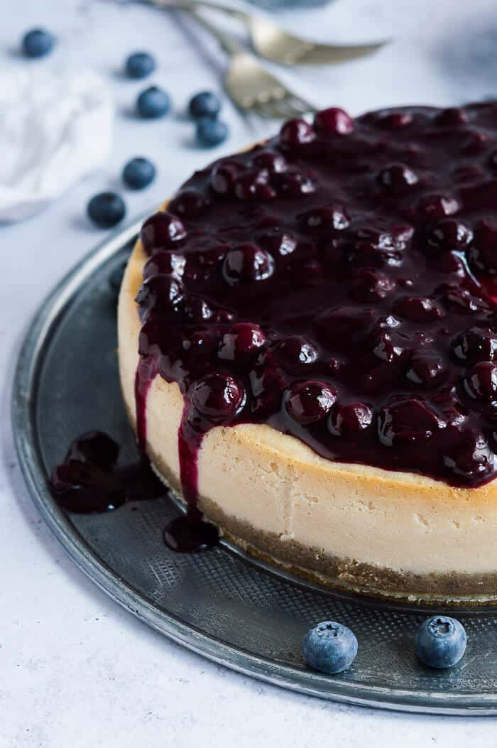 close up of the side of vegan lemon cheesecake topped with blueberry compote