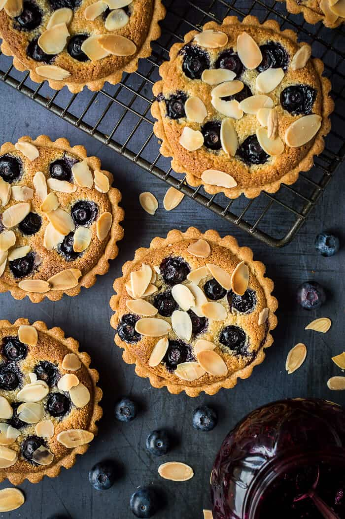 Blueberry frangipane tarts on a metal background and a wire rack with a pot of blueberry jam.