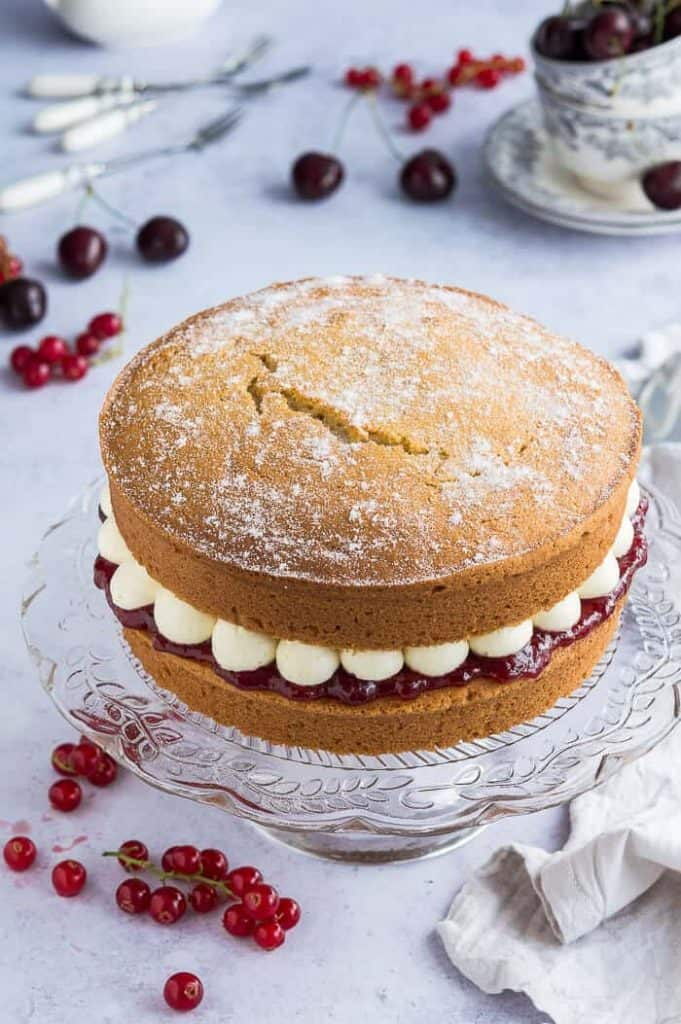 Vegan Victoria sponge cake filled with jam and buttercream on a glass cake stand on a grey background with cherries and redcurrants.