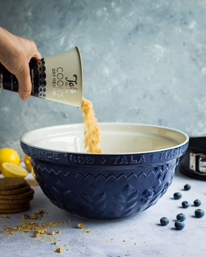 Pouring crushed biscuits into a blue Tala mixing bowl.