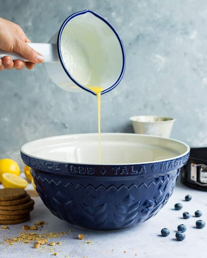 Pouring melted butter into a blue Tala mixing bowl