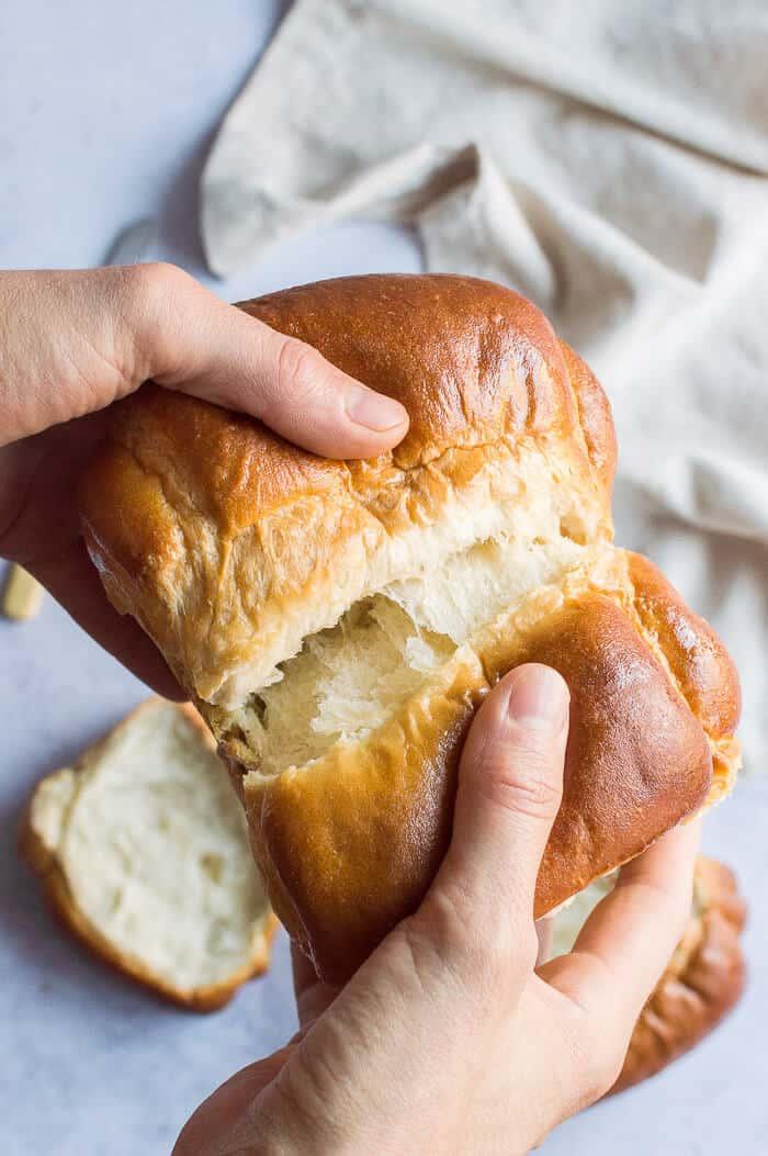 Hands tearing apart a loaf of vegan Hokkaido milk bread