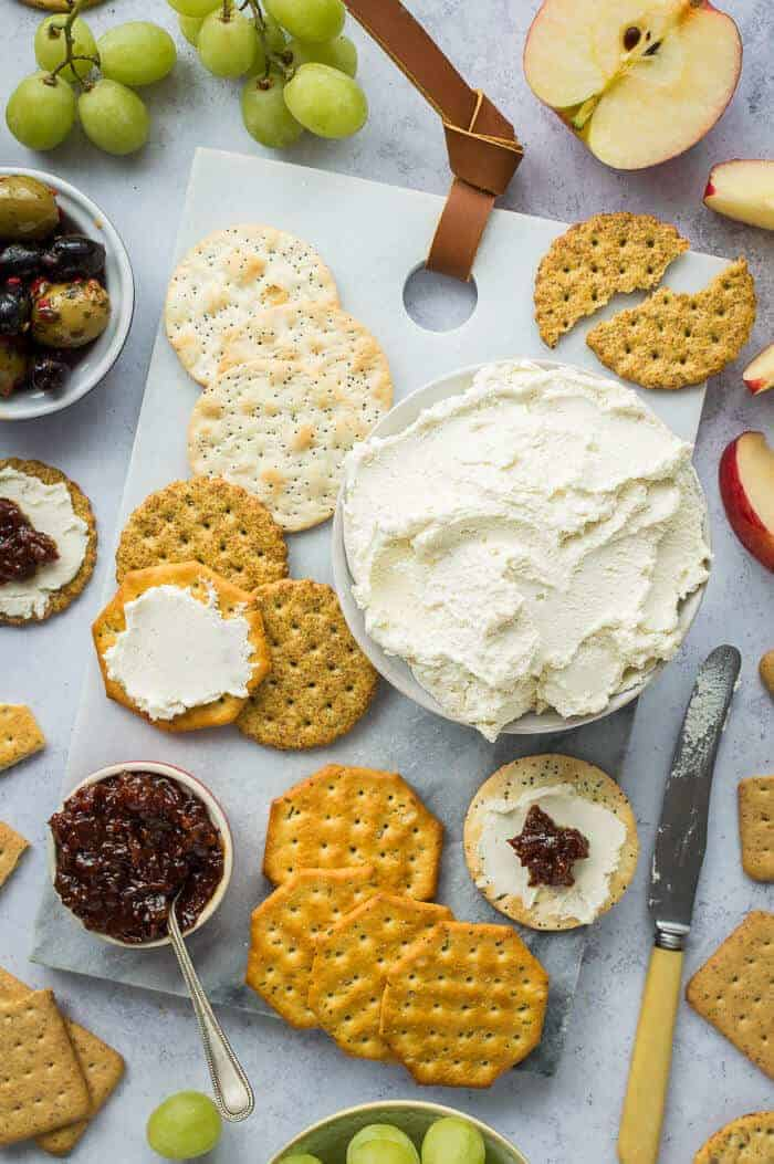 A bowl of vegan almond feta cream cheese on a marble board with crackers, chutney, olives, apple and grapes.