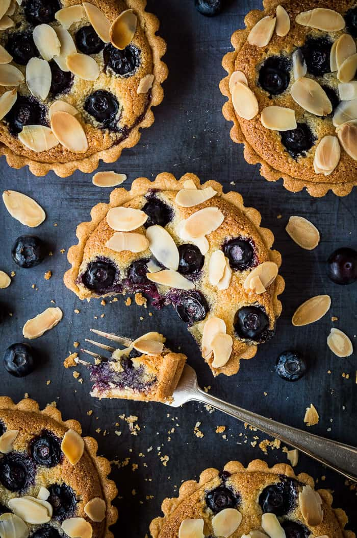 blueberry frangipane tarts on a metal background with a forkful removed.