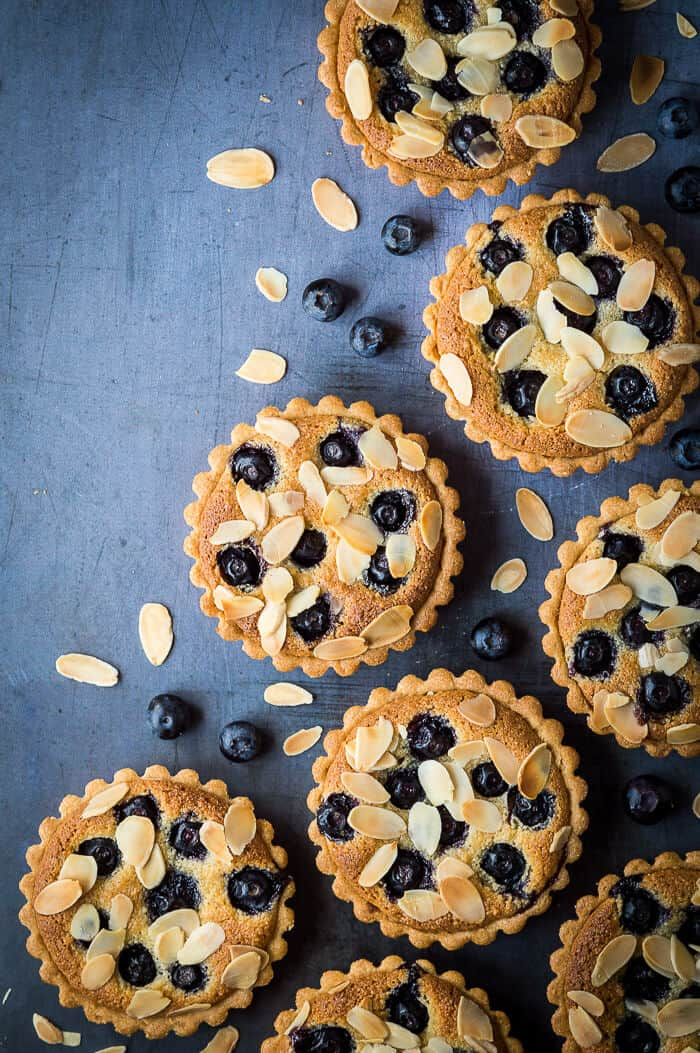 Vegan blueberry tarts arranged on a metal background with fresh blueberries and flaked almonds.