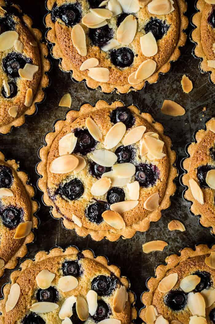 Vegan blueberry frangipane tarts on a dark baking tray.