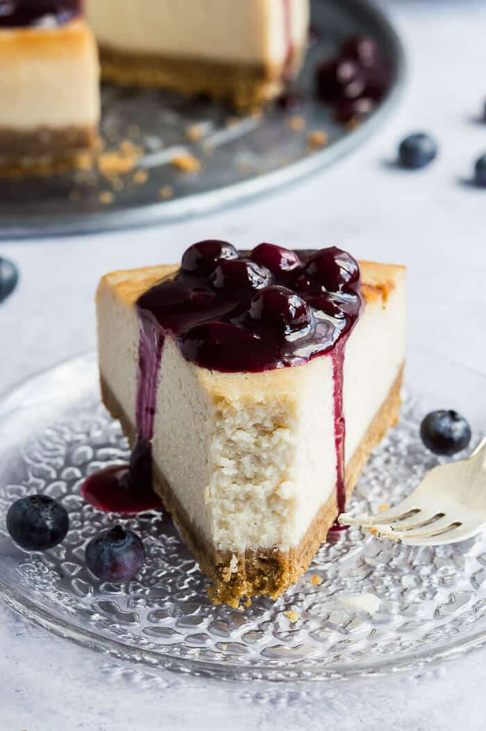 A slice of vegan lemon blueberry cheesecake on a glass plate with a forkful removed.