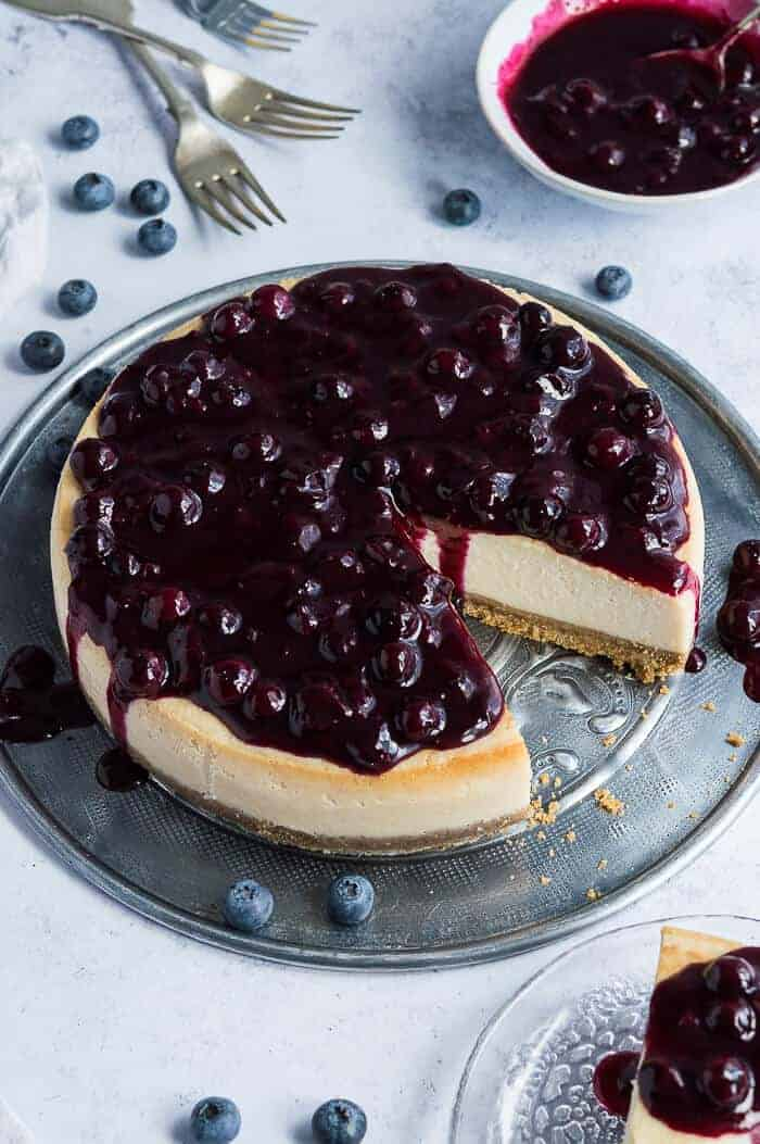 Vegan lemon blueberry cheesecake on a metal plate with blueberries.