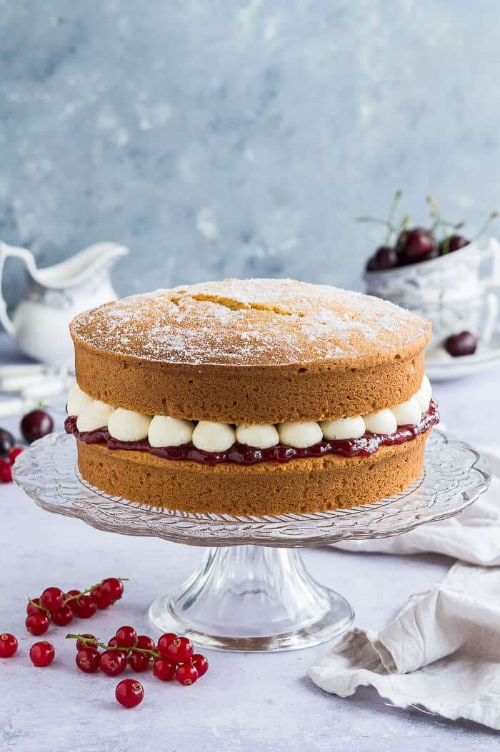 Vegan victoria sponge cake on a glass cake stand with fruit and crockery in the background.