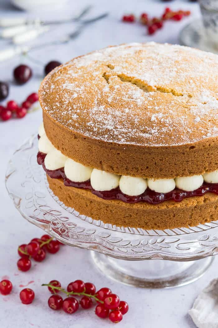 Close up of the side of vegan victoria sponge cake filled with jam and blobs of buttercream on a glass cake stand.
