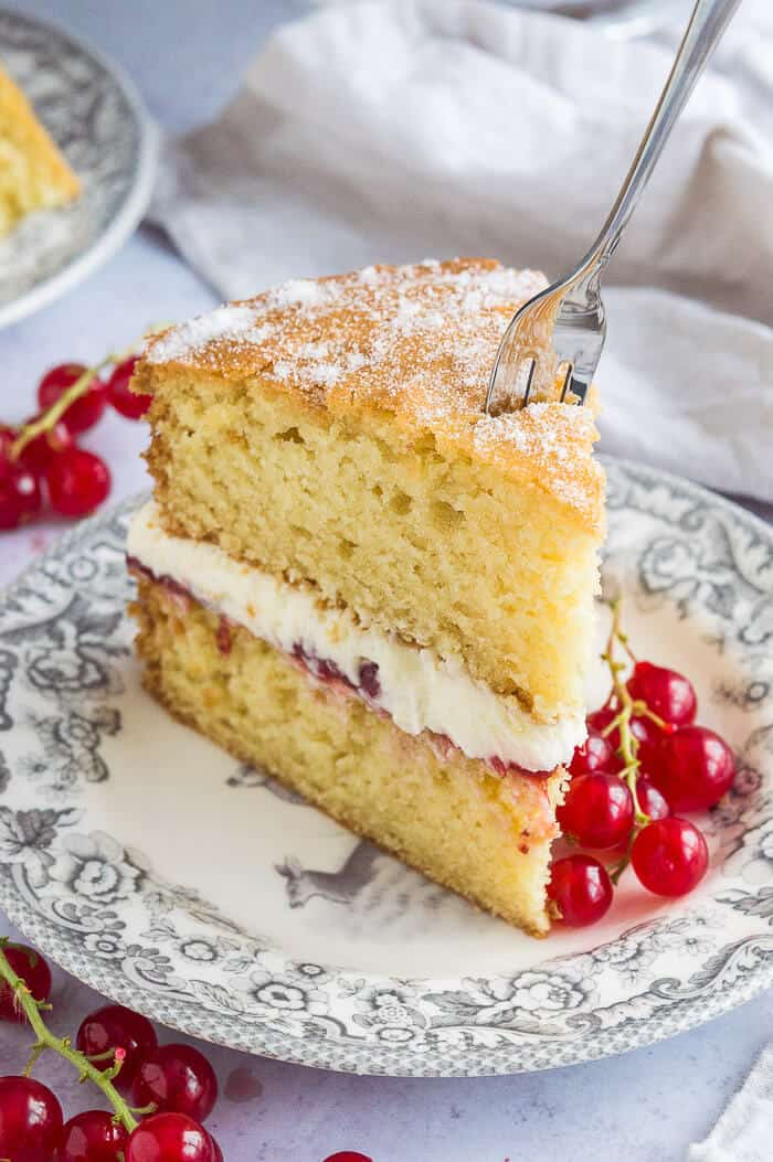 A slice of vegan Victoria sponge cake on a grey patterned plate with a fork sticking in it.