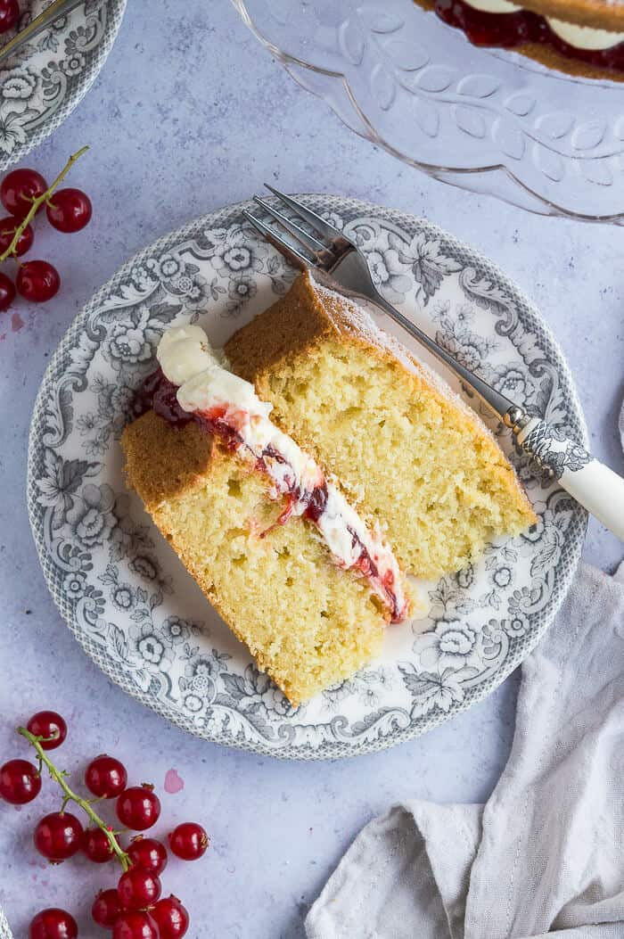 A slice of cake on a grey patterned plate with a cake fork and redcurrants on a grey background.