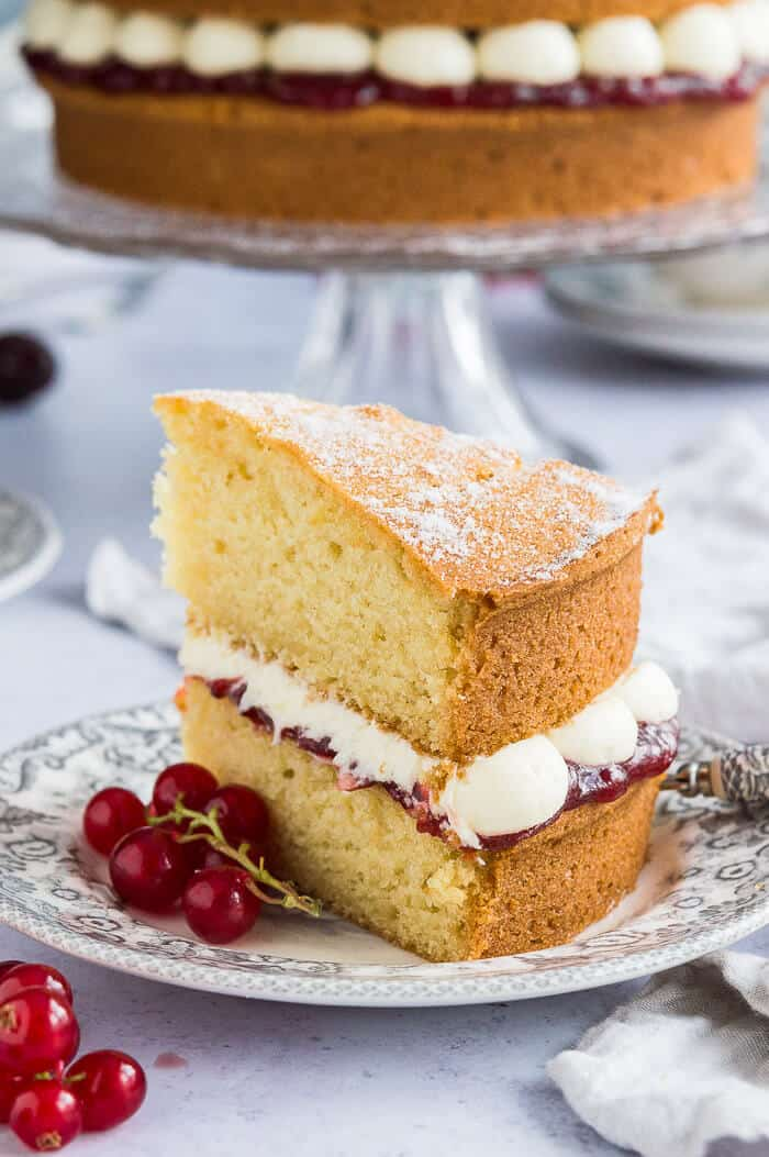 A slice of cake on a grey patterned plate with redcurrants and the whole cake in the background.