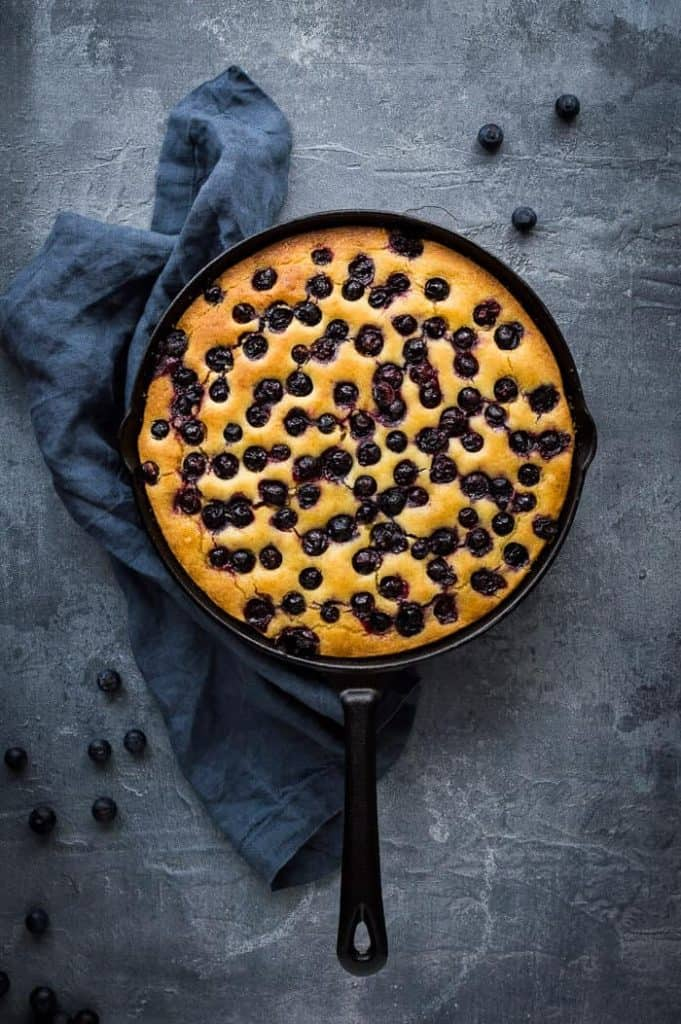 Vegan lemon blueberry polenta cake in a black cast iron skillet on a grey background.