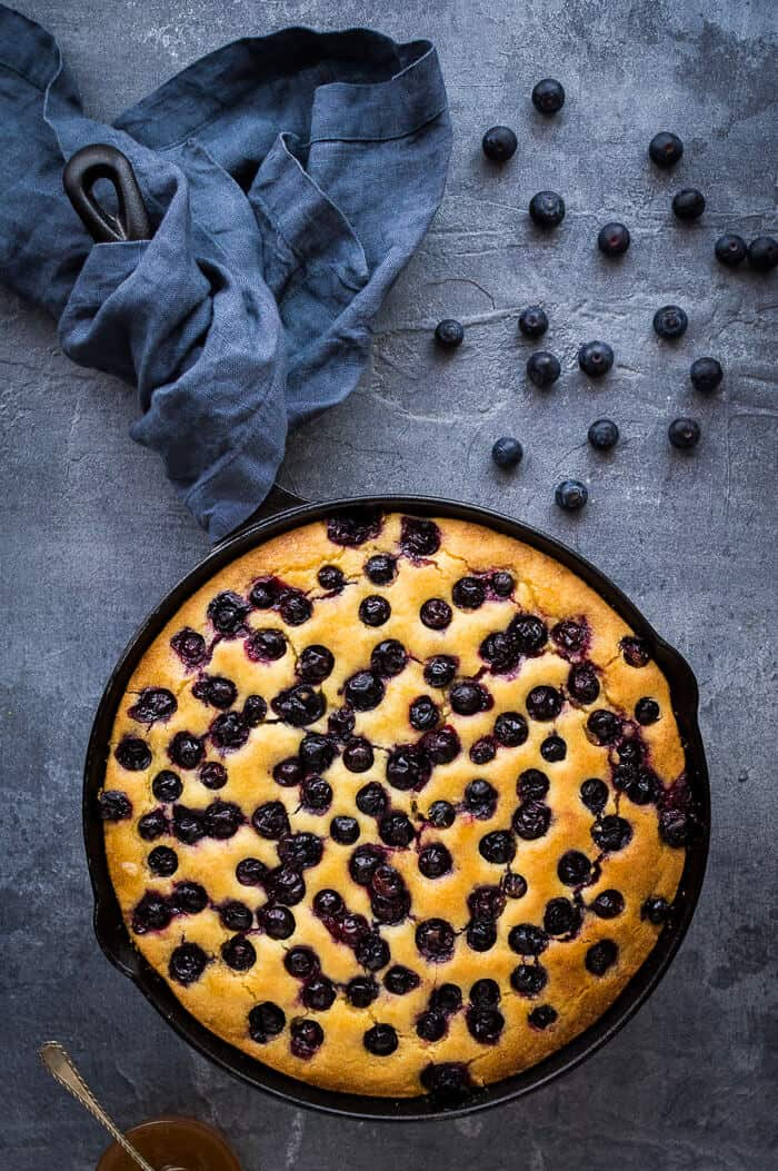 A skillet of lemon blueberry polenta cake on a grey background with a grey cloth and fresh blueberries.