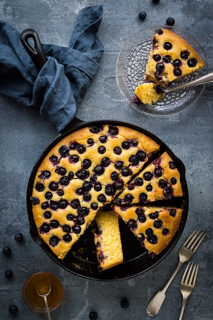 Sliced lemon blueberry polenta cake in a skillet with one slice on a glass plate.