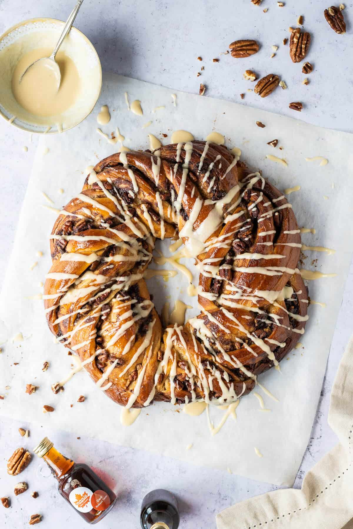 Maple pecan bread wreath from above on a sheet of baking parchment on a grey background.