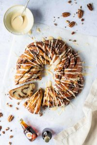Maple pecan bread wreath with two slices cut out on a sheet of baking parchment with a bowl of glaze, pecan nuts and mini bottles of maple syrup.
