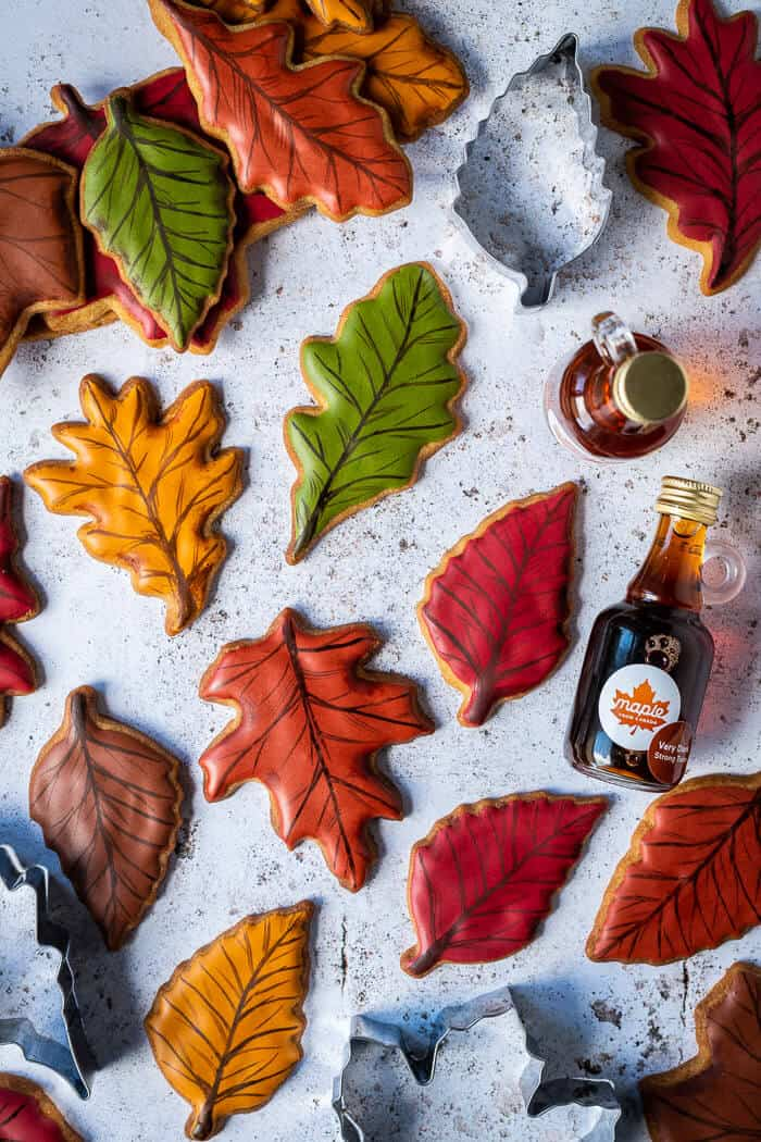 Coloured leaf biscuits on a white background with cookie cutters and bottles of maple syrup.